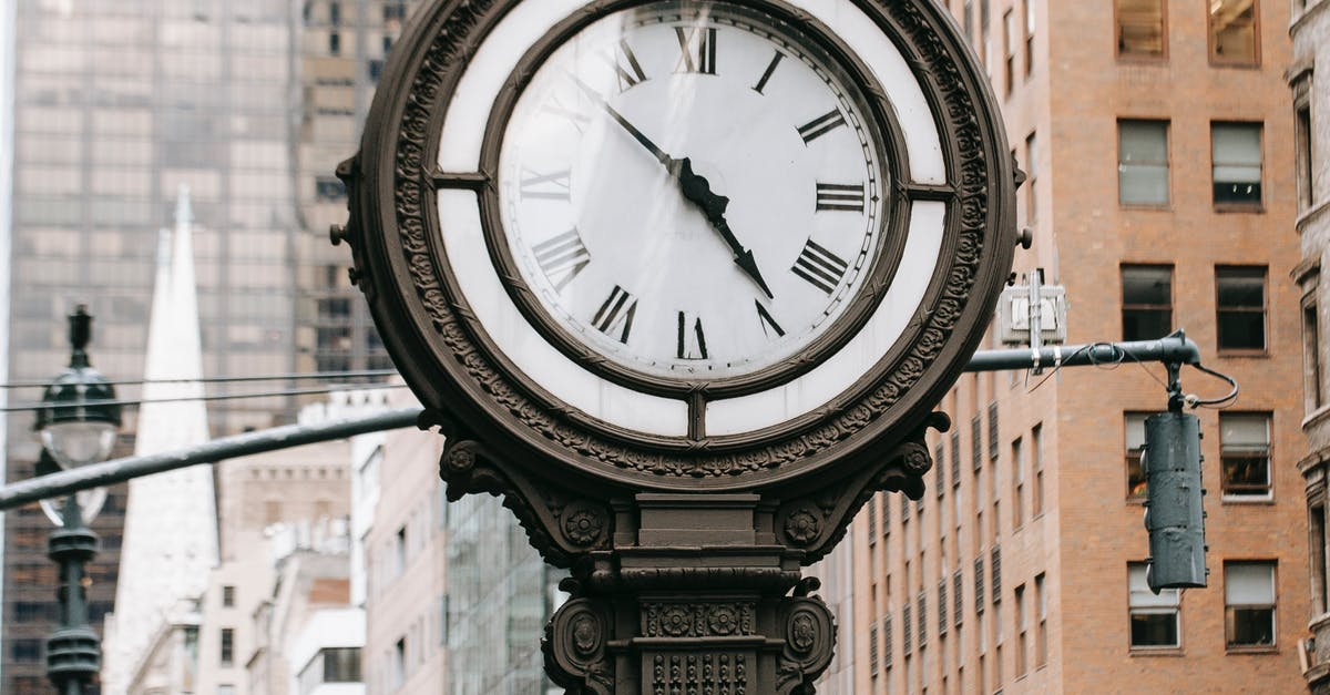 A clock that is on a pole on a city street